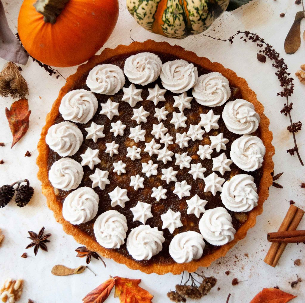 Overhead shot of Pumpkin Walnut Jam Tart on table with autumnal decorations