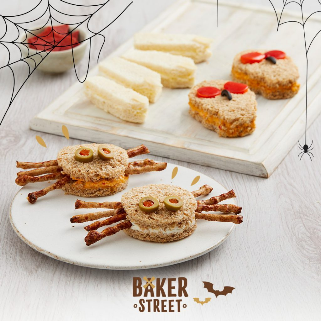 Halloween sandwiches in the shape of spiders, skulls and witches' fingers on a white table